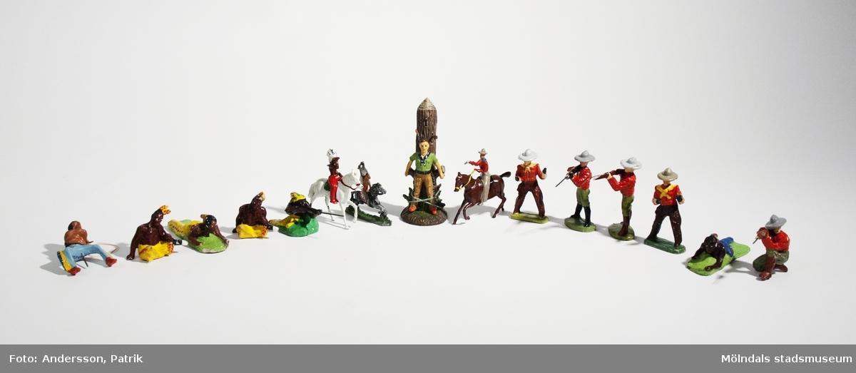 """12 st Elastolin-figurer: 7 st indianer och 5 st cowboys. Tillverkade av O & M Hausser i Tyskland på 1930- och 40-talet. Figurerna är handmålade. Namnet """"Elastolin"""", finns gjutet under mannen vid stocken.Leksakerna är från givarens Lars-Olof Larssons (f. 1940) barndom på 1940-talet.Figurerna är något slitna, men är i bra skick.Denna samling av Elastolin-figurer förvarade givaren i ett skrin (MM04943) tillsammans med andra tennfiguer (MM04944:2).MåttLängd: cirka 75 mm i genomsnitt (stående cowboy)Längd: cirka 44 mm i genomsnitt (sittande indian)Längd: 115 mm (mannen vid stocken)"""