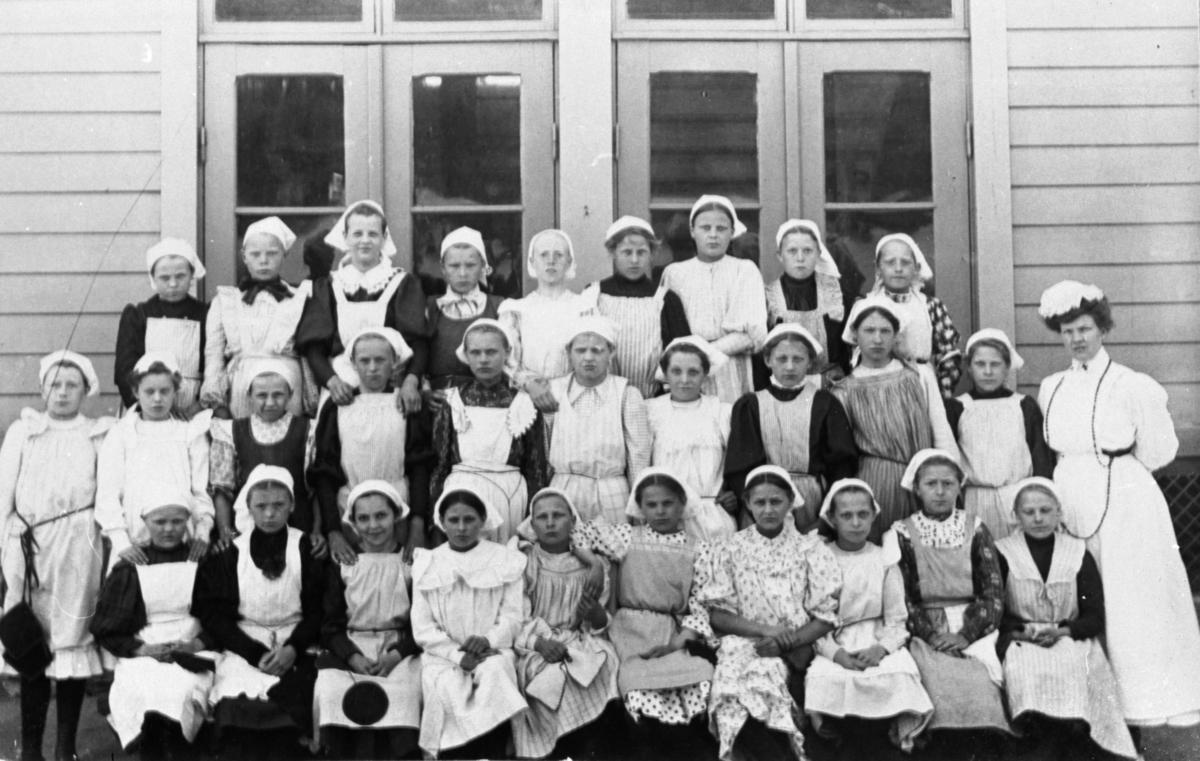 Flickor utanför Trädgårdsskolan, klädda i skolkökskläder.