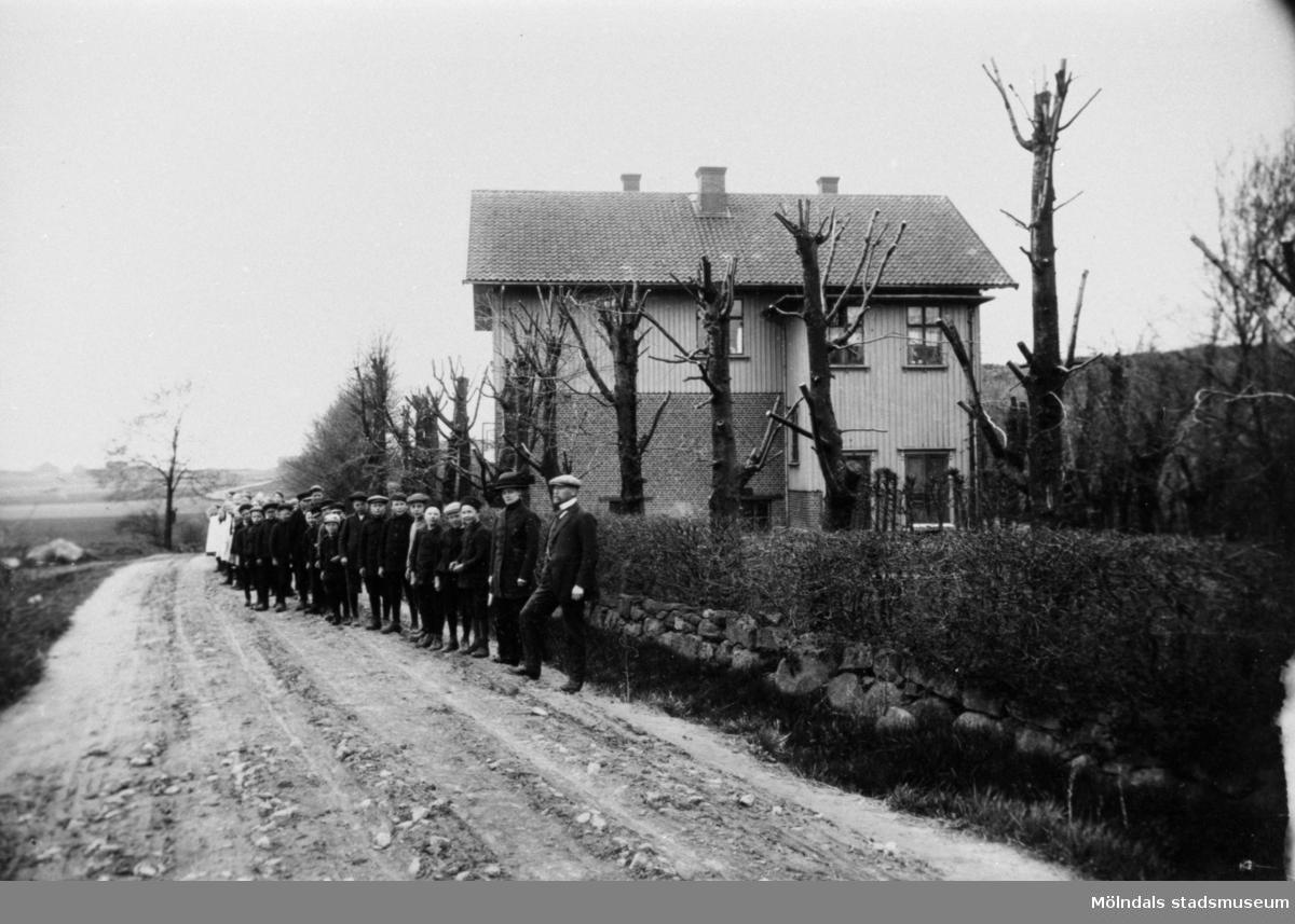 Gamla Fässbergsskolan vid 1900-talets början.  Mannen längst till höger är magister Otto Björstedt.