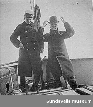 Två män på däcket till segelbåt.