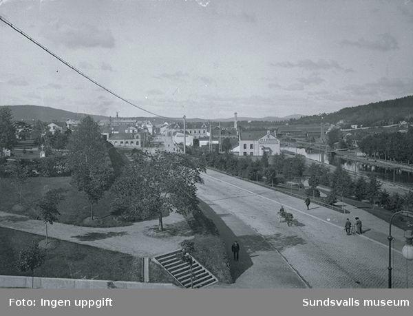 """Storgatans västra del,kyrkan till vänster om Storgatan och till höger Selångersån,Norrmalm.I bakgrunden syns ett fabriks och industriområde,synlig text"""" SNICKERIFABRIK , JOH.D.GRUNDBERGS WATTENLEDNINGSAFFÄR REPARATIONSVERKSTAD"""". Ångbageri."""