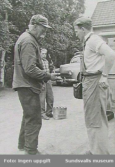 Sundsvallsbryggerier AB. Chauffören Georg Staaf tar betalt av en kund vid leverans.