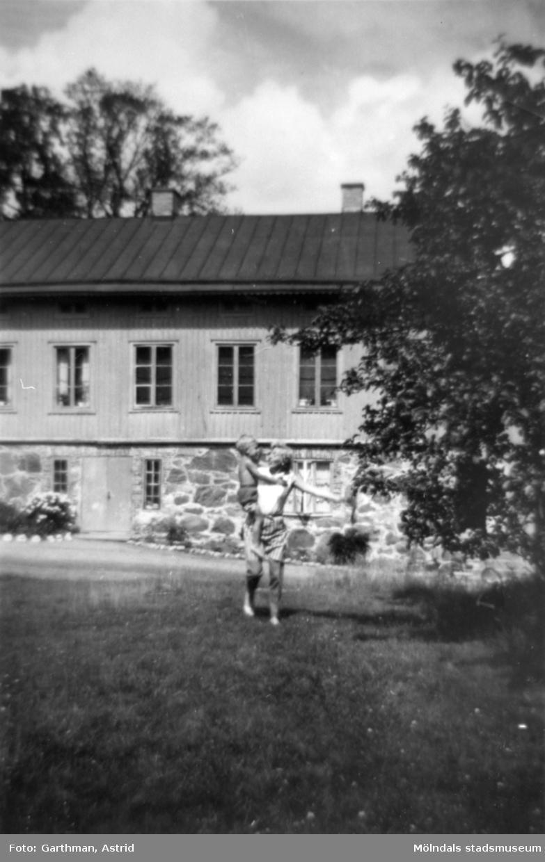 """Astrid Garthmans syster Ingrid Karlsson håller sin son Lars i famnen. Man ser Solbacken eller """"Skogsvaktarebostaden"""" i bakgrunden. Gunnebo, 1960-tal."""
