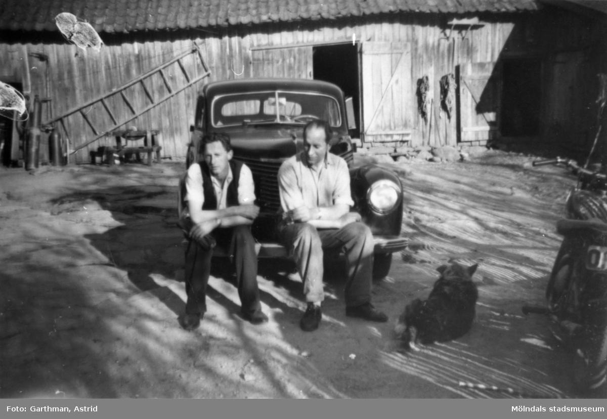 Birger och Herbert Lyckö sitter på stänkskärmen till en Opel Kapitän. På marken vid sidan om ligger en hund. I bakgrunden ser man en lada med en stege hängandes på väggen. Kvarnfallet i Mölndal, 1940-50-tal.