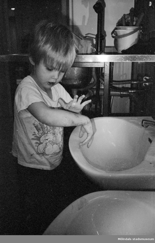 Ett dagisbarn tvättar händerna vid ett litet handfat för barn. Katrinebergs daghem, 1992-93.