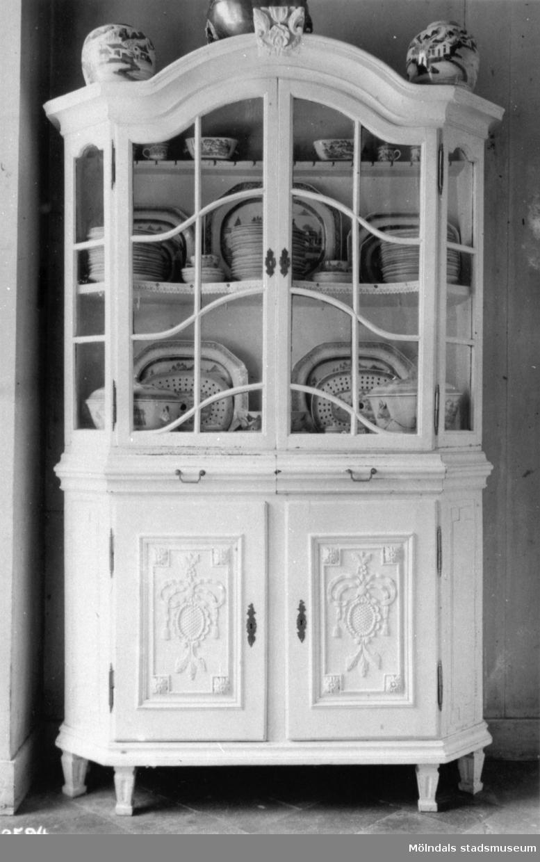 Vitrinskåp i ljus färg med ett par inglasade dörrar upptill och två luckor nertill. Skåpet innehåller porslinsföremål. Gunnebo slott 1930-tal.