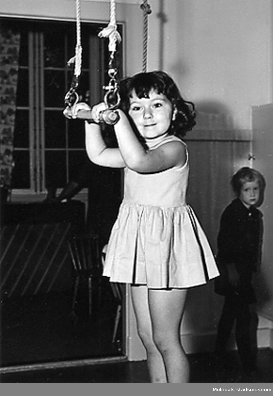 En flicka som leker med en trapets hängande från taket vid Holtermanska daghemmet 1953.