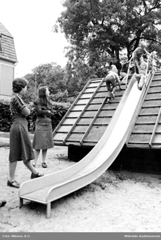 Barn åker rutschbana och två fröknar håller koll. Holtermanska daghemmet 1973.