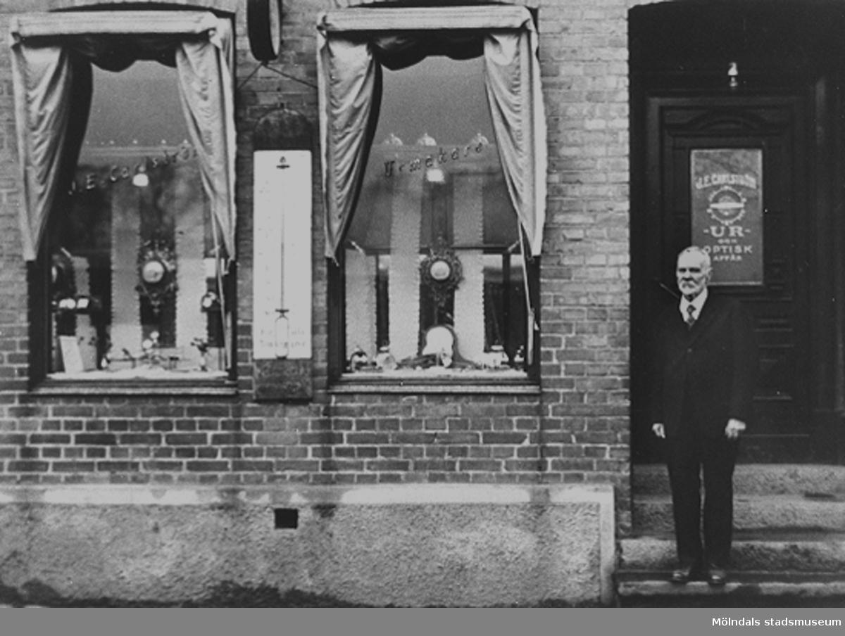 Carlström står utanför sin urmakaraffär som låg ett par hus bort från Gamla torget på Kvarnbygatan 33, 1920-tal. Senare inrymdes Bergs kaffehandel i denna lokal. Huset är rivet.