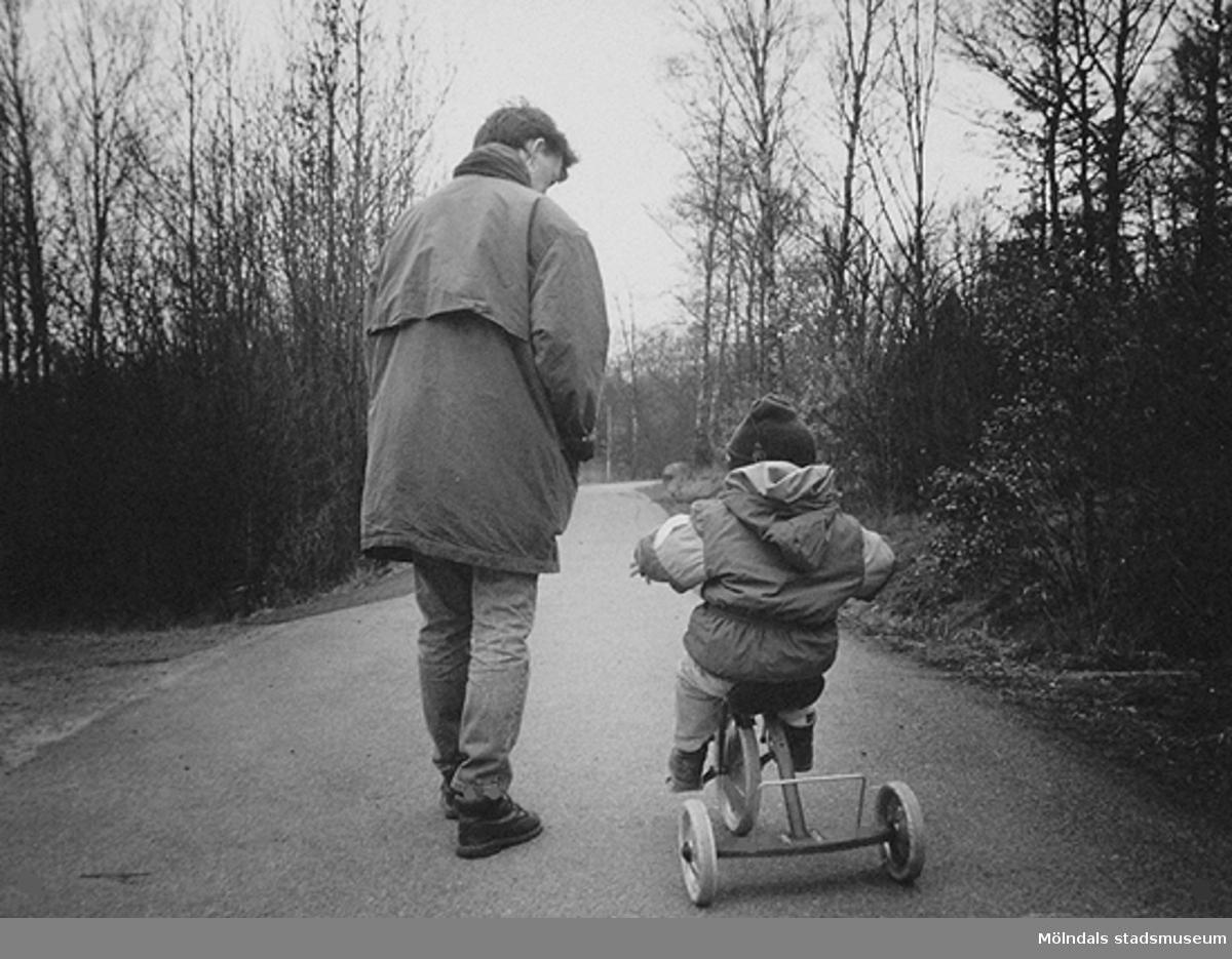 """Ett litet barn som cyklar på en trehjuling och en kvinna går bredvid.Bild som användes vid utställningen """"Är du inte riktigt klok?"""" på Mölndals museum 1990."""