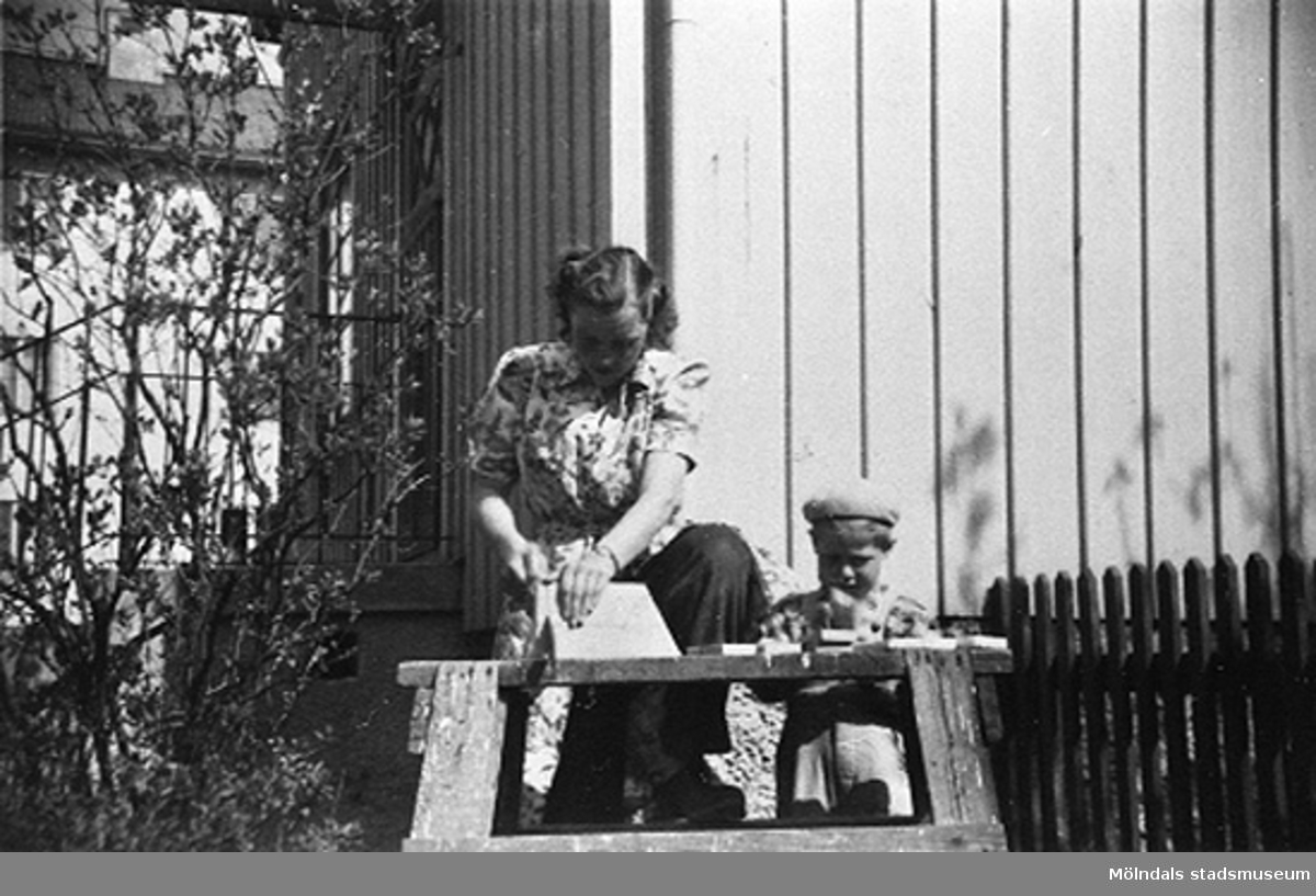 En lärare och ett barn sågar någonting i trädgården.Krokslätts daghem, Dalhemsgatan 7 i Krokslätt 1949.