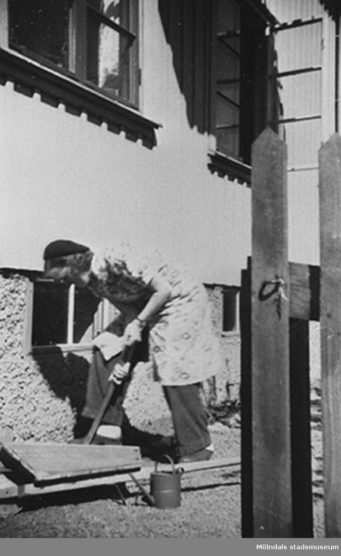 En lärare planterar blommor utefter väggen vid Krokslätts daghem, Dalhemsgatan 7 i Krokslätt år 1949.
