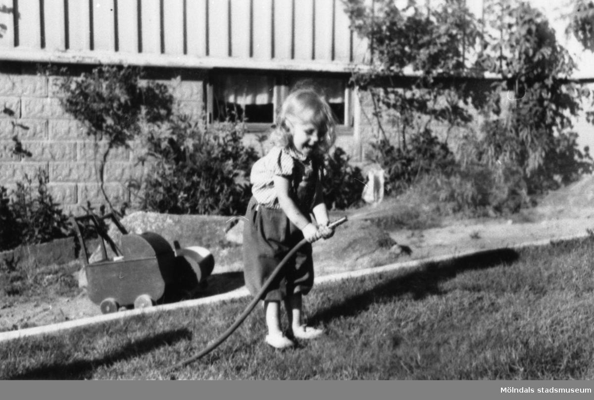 Karin Hansson f. Pettersson sprutar vatten med en trädgårdsslang, Gamlehagsvägen i Torrekulla, ca 1950.