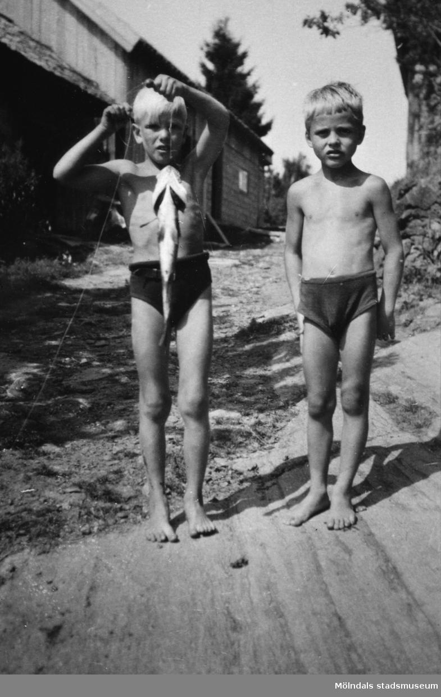 Två pojkar som har fiskat, cirka 1930.