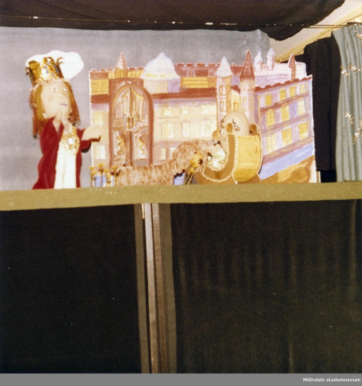 """Föreställning av """"Den förtrollade fisken"""" i TBV:s lokal, mars 1981. Fotografi ur album tillhörande Blanka Kaplan.  Sagan om den förtrollade fisken är en bearbetning Blanka Kaplan gjort av sagan """"Fiskaren och hans hustru"""". Den gick som dockföreställning under året -81 till början av -82 i TBV-husets lokal på Hagåkersgatan 4 i Mölndal.  Den handlar i korthet om en fiskare som en dag får upp en förtrollad flundra på kroken. Fiskarens hustru begär då att fiskaren ska be flundran att förvandla deras fattiga koja till en nätt liten stuga. Flundran uppfyller önskningen, men hustrun vill snart ha mer och mer och blir med tiden både kejsare och påve. Till sist önskar hon sig för mycket."""
