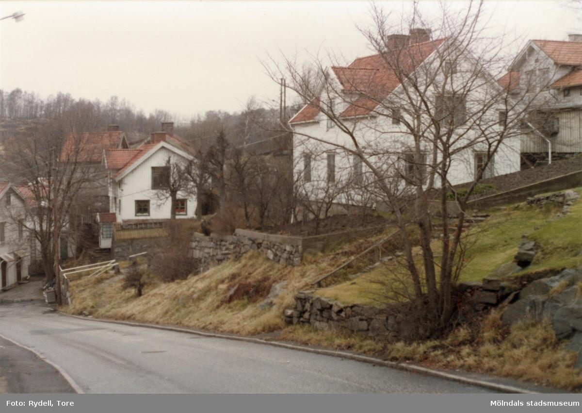 """Hus vid Rygatan i Mölndal. Till vänster ses Roten M 28, även kallat """"Falkebot"""", till höger Roten L 12, även kallat """"Nabbens hus"""".Fotografi ur album som tillhört Christina Rydell. Bilderna i albumen är delvis från Papyrus där Christinas far Tore Rydell arbetade, men också från Kvarnbyn, Ryet och folkliv i Mölndal. Tore tog ofta med sig kameran till Papyrus där han fotograferade sina arbetskamrater i arbete, men också fester och föreningsliv."""