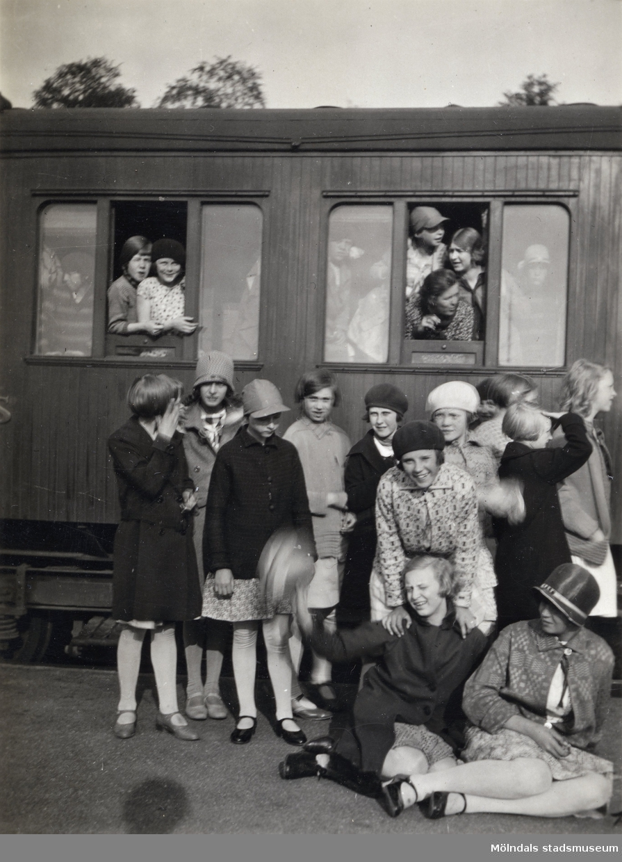 En samling flickor fotograferade framför en järnvägsvagn. En av flickorna är Elna Börjesson. Fotografi ur album som tillhört Åke Börjesson.