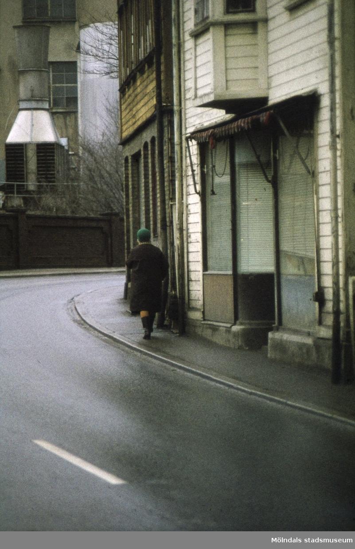 Gående kvinna utanför Kvarnbygatan 33 och 35 i Mölndal, 1970-tal. I bakgrunden ses även byggnad tillhörande Papyrus.