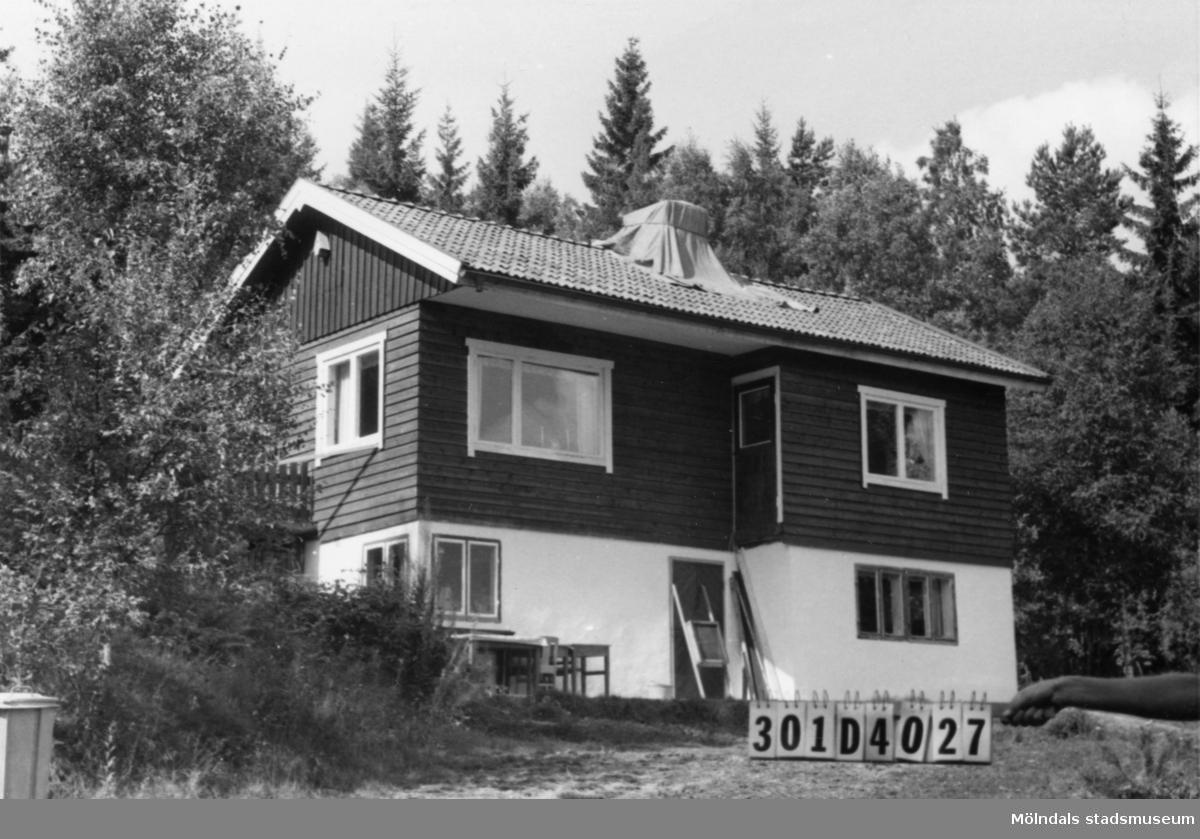 Byggnadsinventering i Lindome 1968. Hällesåker 5:12. Hus nr: 301D4027. Benämning: fritidshus. Kvalitet: mycket god. Material: trä. Övrigt: hög, ful sockel på ett i övrigt fint hus. Tillfartsväg: framkomlig. Renhållning: soptömning.