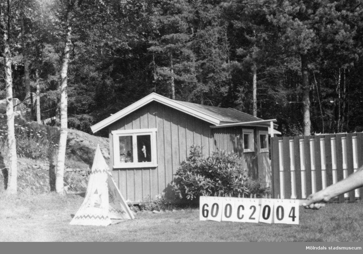 Byggnadsinventering i Lindome 1968. Strekered 1:20. Hus nr: 600C2004. Benämning: två fritidshus och redskapsbod. Kvalitet, bostadshus: det ena god (trä), det andra mindre god (masonite). Kvalitet, redskapsbod: god. Material, bostadshus: det ena trä, det andra masonite. Material, redskapsbod: trä. Tillfartsväg: framkomlig. Renhållning: soptömning.