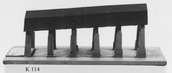 Modell av skeppsskjul, troligen Vasaskjul, med sex dubbla pelare och brutet tak men utan väggar. Taket avdelat i sex tvärsgående delar. Pelarna står på en träplatta. Taket är svartmålat, övrigt grått.