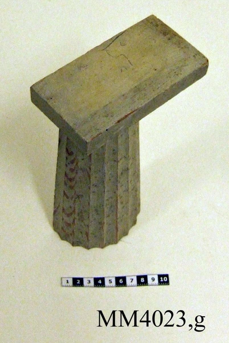 """Pelare, eller kolonner, släta och räfflade (7 st halvkolonner, räfflade). 20 st. modeller av trä, avsedda som fasadprydnader. Pelarna är räfflade med halvcirkelformig basyta. De är vitmålade. Kapitälen är av närmast dorisk stil. Pelarna utgör modeller till gavelkonstruktion för nya inventariekammaren på varvet 1785-87. De sammanhängs troligen med en serie av gavelmodeller och pelare, som finns i kistan i sal 1 och vid norra delen av väggen i samma sal. (K 2244)  Halvkolonn, kannelerad med kapitäl och fast abakus. Målad i gråvitt.  Tidigare märkt: """"5"""" """"2244""""."""