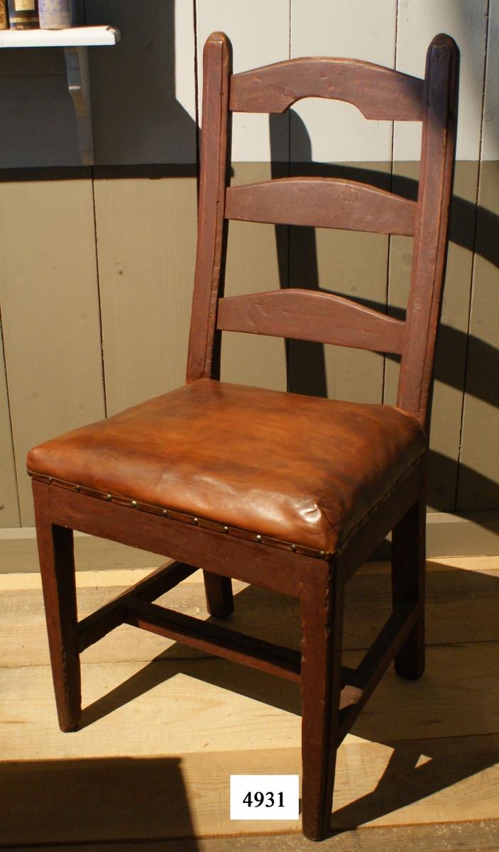 Stol av björk, rödmålad. Benen är fyrkantiga och sammanhålles av tre fyrkantiga slåar, sk. H-kryss. Rygg med tre tvärslåar, det översta med urtag i underkanten. Sitsen är klädd med skinn. Stolen härstammar från senare delen av 1700-talet.