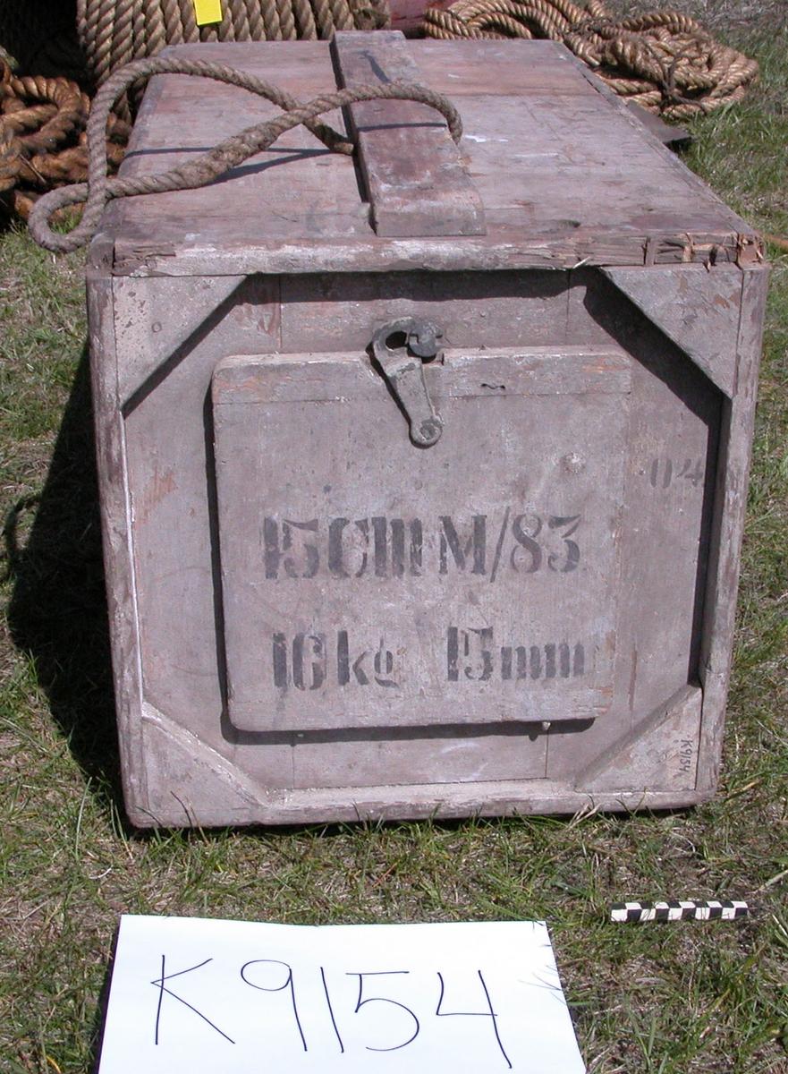 Av koppar, utvändigt klädd med trä, vitmålat, invändigt förtent. Fyrkantig. På översidan runt hål med löst lock. Över detta fyrkantig lucka av trä på gångjärn, vilken låses med rörlig hake och skruv. Utvändigt  på två sidor släplister av trä med bärhandtag av rep. Märkning: 15 cm. M/83 16 kg. 15 cm 04.