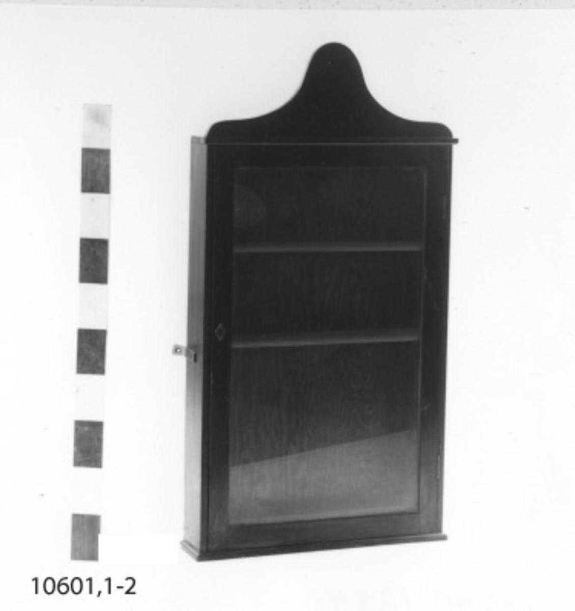 Skåp av mahogny. Med glasdörrar och tre hyllor. Ovan skåpet en halvcirkelformad bräda, på vilken ett emblem varit placerat.
