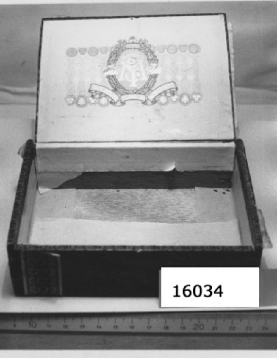 """Cigarrlåda med sjömansmynt 154 st lista! Cigarrask i brunt poröst trä, med ovansidan som lock. Asken klistrad, därefter pappersremsor med svenska tobaksmonopolets emblem i svart mot röd bakgrund och gulddekor, klistrade om kanterna. Plomberingsbanderoll i grönt och vitt om vänstra sidan med svenska tobaksmonopolets kontrollstämpel, samt prisuppgift; """"Pris pr 1st. 15 öre"""" """"50"""" 7,50 kr"""" På högra sidan pappersetikett påklistrad i rött svart, guld med texten; """"MARCA SELECTA No210 AB SVENSKA TOBAKSMONOPOLET"""" I lockets ovansida i djuptryck, """"STM:s emblem i vitt, blått och guld. Asken innehåller 154 småmynt av följande nationalitet och valör; Sverge; 5 öre 1923, 5 öre 1691, okänt 1713 (cx11) 3 st 1 öre 1921, 1935,1926. Flertalet mynt går att avläsa. Se katalogkort. Förutom mynt ínnehåller asken: 1 st djurkoppel av metallöglor,1 st emblem av metall, i formen av en lyra, 1 st brosch, cirkelrunt med justitia stående med vågskålen samt texten: SVF FRA JUS G11, i relief."""