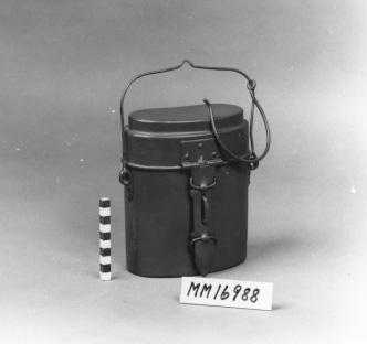 """Kokkärl. Behållare av aluminium med lock, utvändigt grönmålad. Locket är försett med handtag på gångjärn så att locket kan användas för tillagning av mat. Handtaget fungerar även som lås mot behållaren. Behållaren är försedd med bygelhandtag av metalltråd med krok för upphängning. Stämplat på framsidan """"I R 5K"""" No 214. Kallas även snuskburk. Tillsammans med kokkärlet hörde även ett enmanskök som ej finns här."""