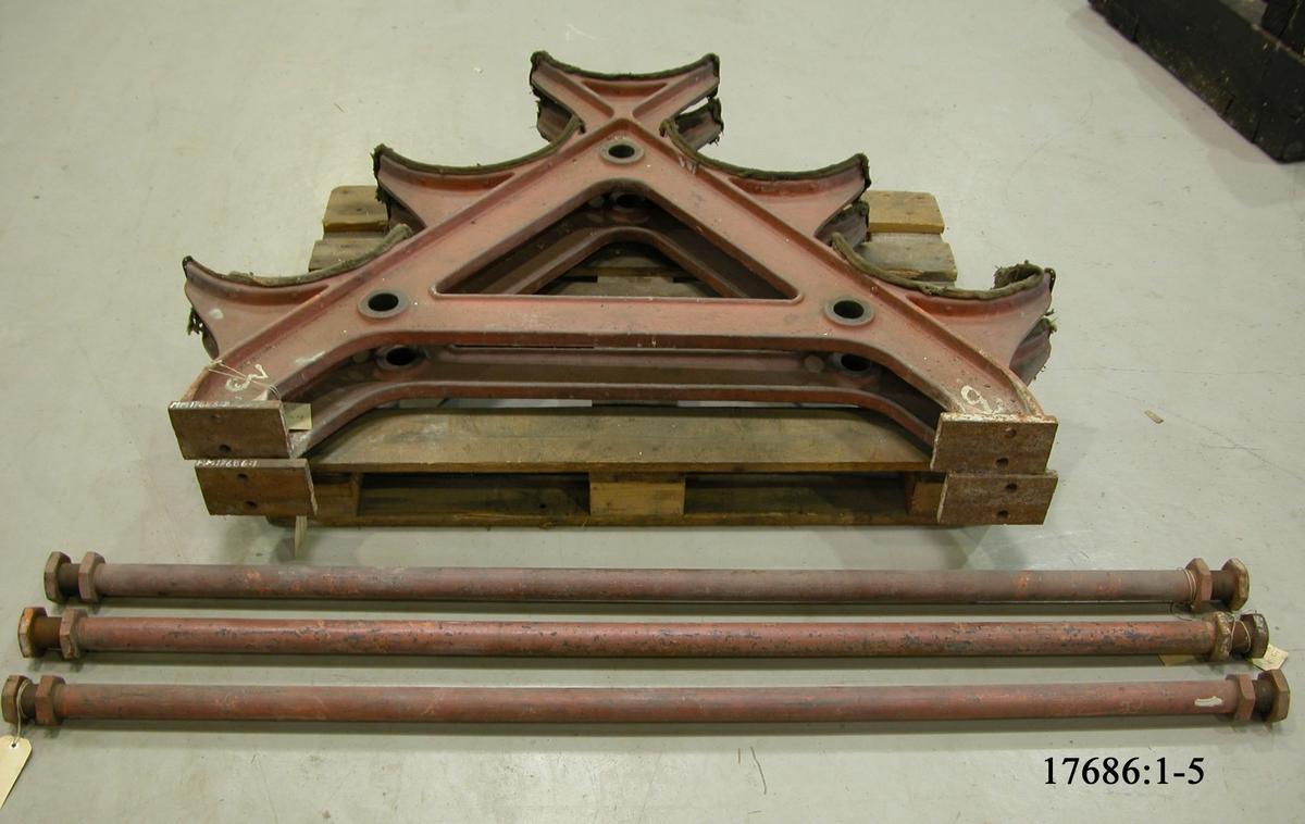Torpedställning av gjutjärn bestående av två ben, formade som ett A med fem hyllor för placering av torpeder. Benen hålles samman med tre järnrör,  som sättes in i hål genom benen och skruvas på plats. Hyllorna på ställningens ben är klädda med grovvävd textil. Hela ställningen är målad i ljus rött.