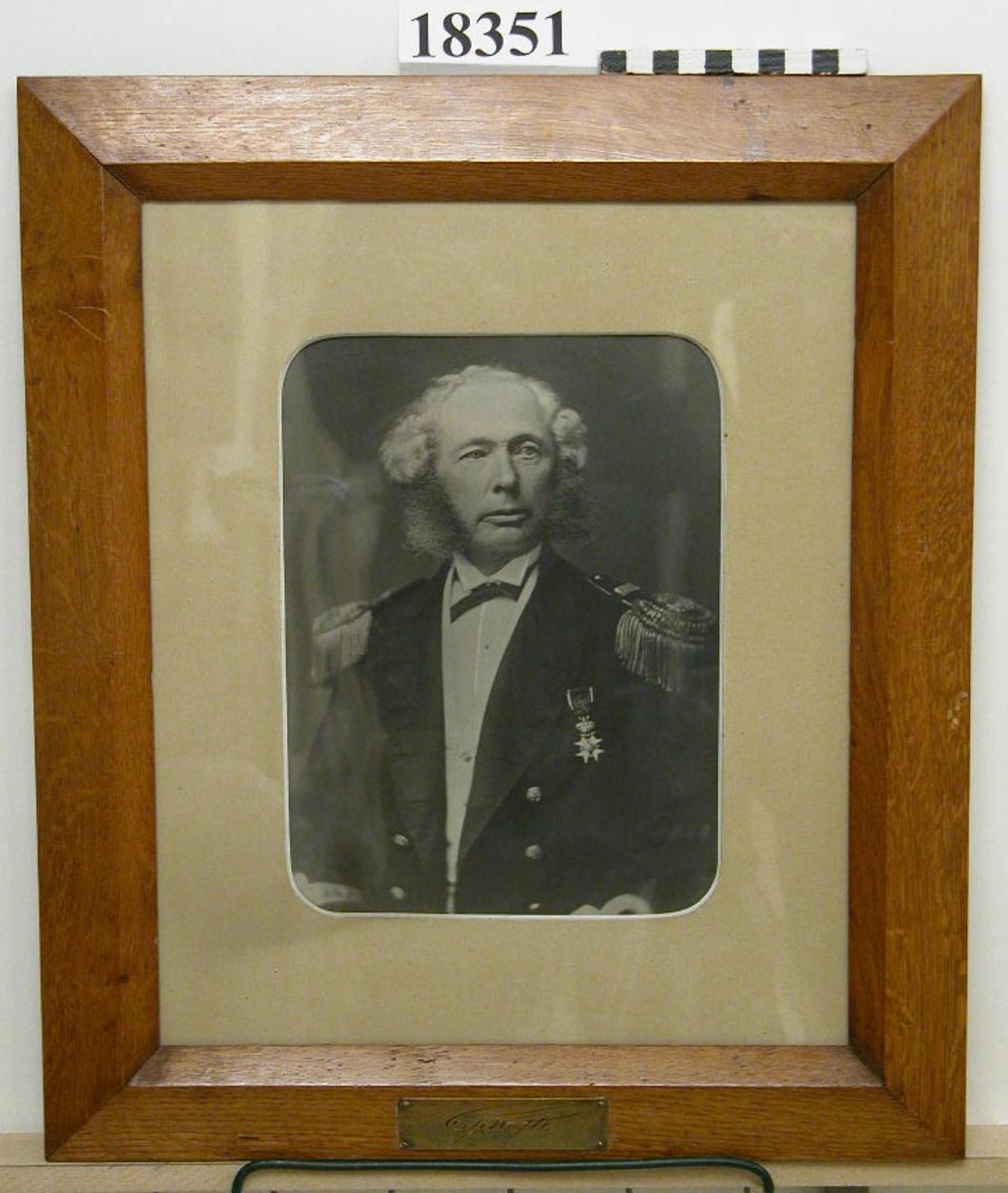 """Fotografi inom glas och ram föreställande C.F. Kafle. Bröstbild av man klädd i uniform med epåletter, en medalj, vitt hår och breda polisonger. Passepartout  B = ca 50 mm. Ram av ljus ek fernissad, profilerad. Nederst mässingsbricka med graverat namn efter namnteckning: """" C.Fr. Kafle """". Baksida kartong försedd med lapp: """" Claes Johan Fredrik Kafle född 1819 7/4 död 1902 25/11 chef 1872-75 """". Neg.nr A 376 2:19"""