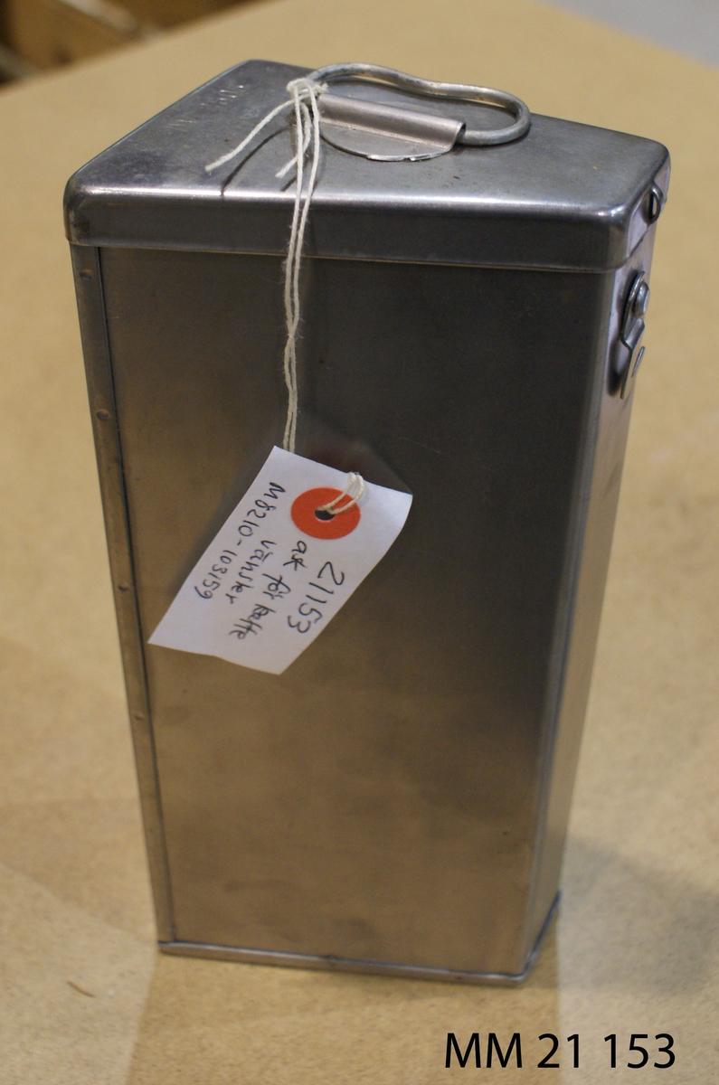 """Ask av rostfritt stål, trekantig form. Lock med bygelhandtag på ovansidan. Märkt """"DV 2505"""" Locket vänt åt vänster."""