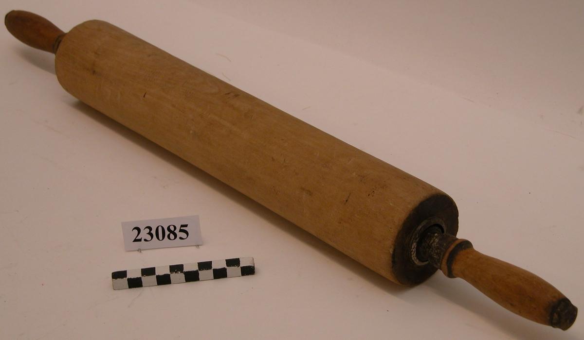 En träkavel som har en genomgående kullagrad metallaxel försedd med trähandtag. Handtagen hålls fast på axeln med ett inre metallbeslag och en yttre sexkantig mutter.