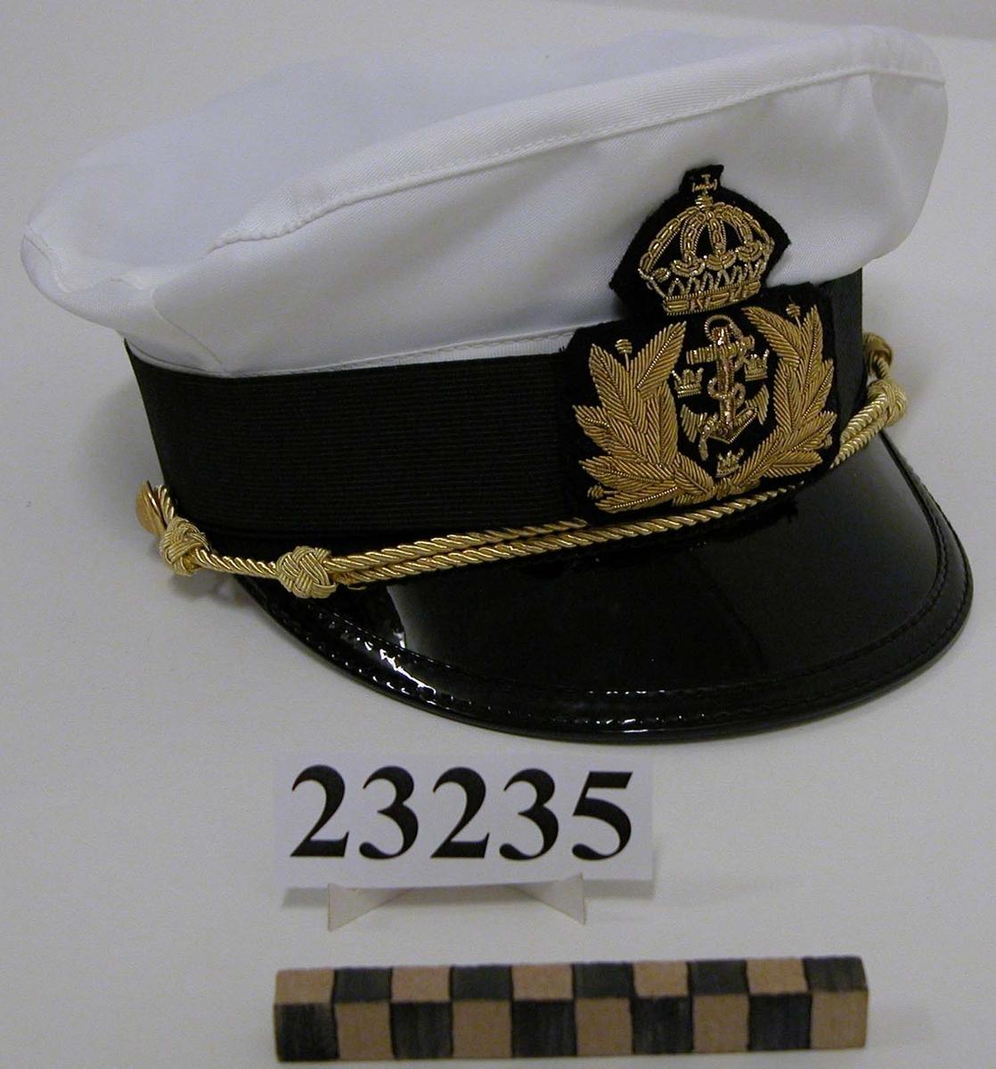 Skärmmössa för officer eller underofficer (kapten-sergeant) vid flottan. Försedd med knapp m/1878 samt snodd för graderna sergeant till kapten.  Stomme i svart kappel i vitt. Kapellet är av syntetiskt material. Skärmen är blanksvart. Storlek 56.