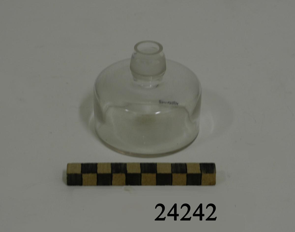 Rund, låg flaska med kort, smal hals av transparant glas. Flaskhalsens metallfäste för veken saknas.