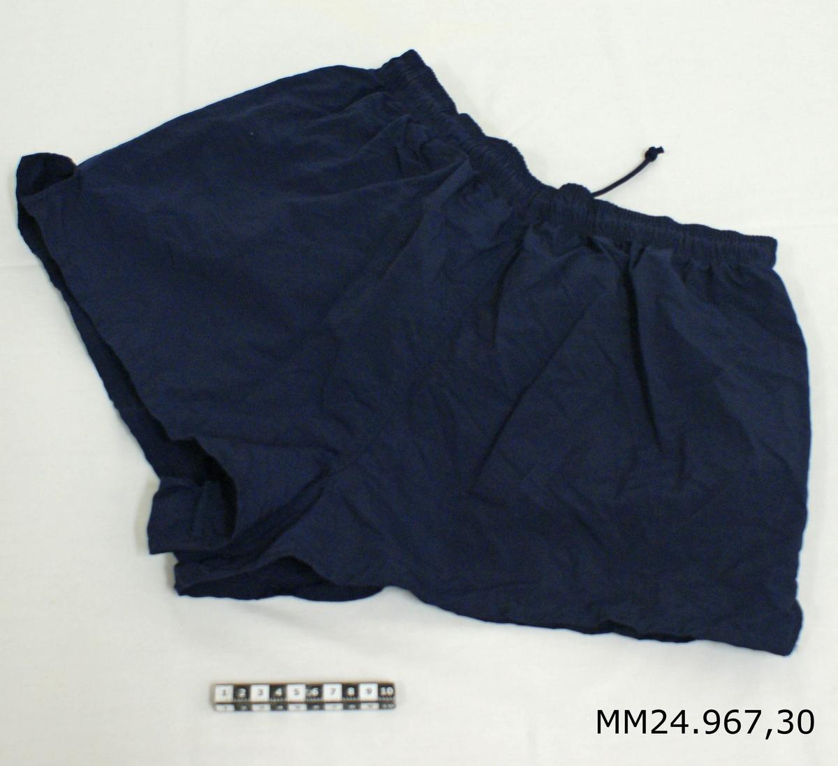 """Idrottsshorts av bomull, polyester och polyamid, mörkblå. Korta shorts med resår och snörning i midjan. Små sprund på shortsens nederkant. Mörkblått foder samt liten innerficka på höger sida. Vitlapp på insidan med kronstämpel, M-nummer, tvättråd, årtalet 1999, vikt 80-95 kg, storlek 6, samt texten: """"AB Blåkläder, tillverkad i Vietnam""""."""