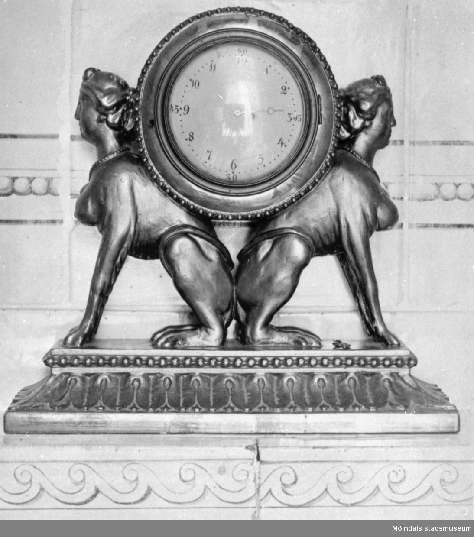 Bordspendyl som på varje sida bärs upp av figurer med kvinnlig överkropp och sittande djurkropp. Gunnebo slott 1930-tal.