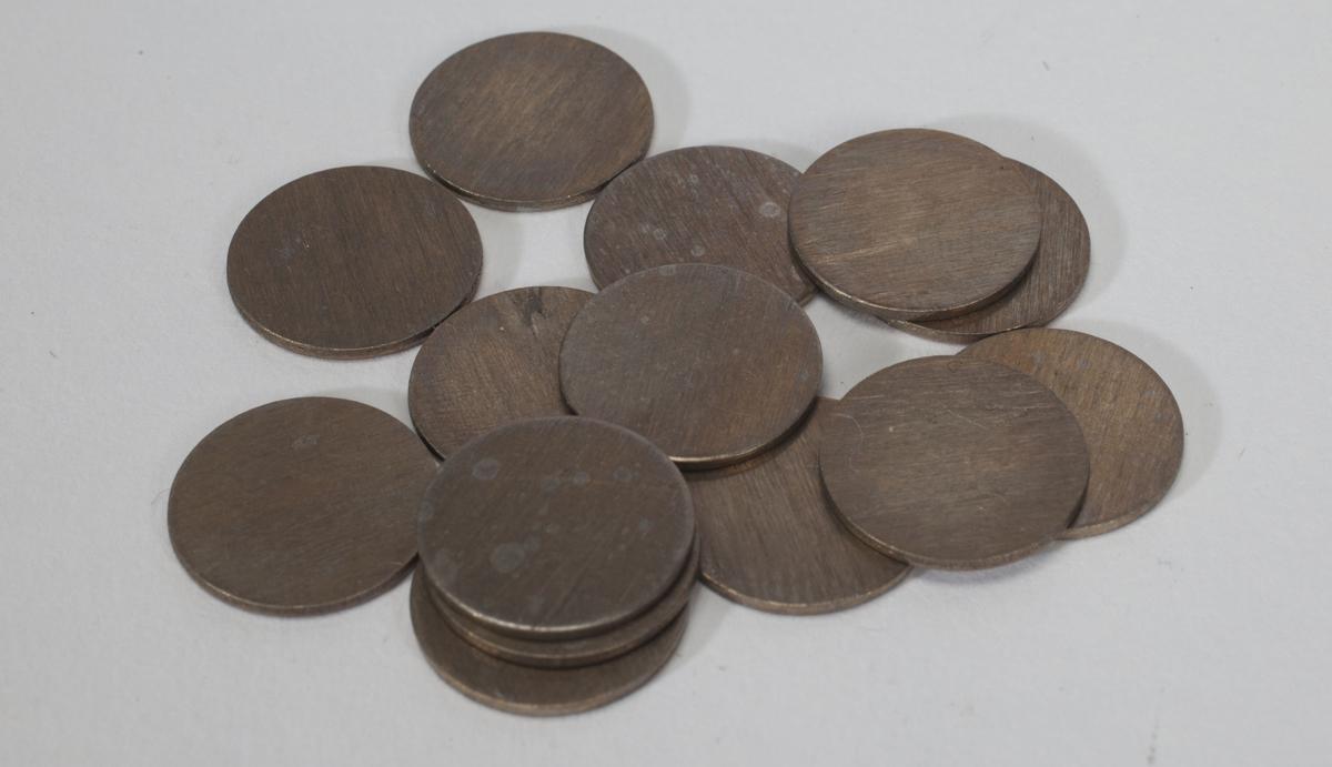 Fjorten runde metallplater.