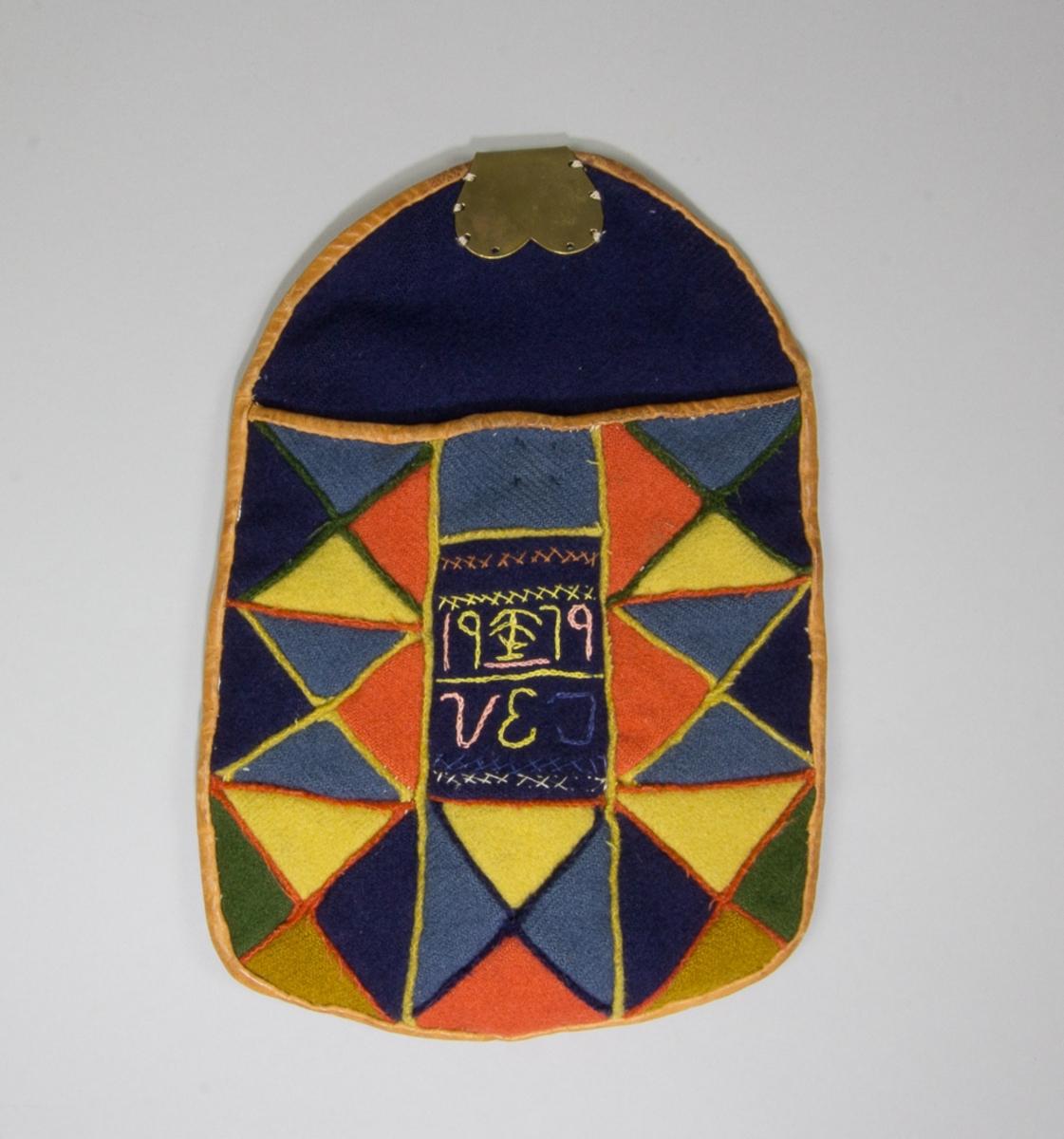 Kjolsäck till dräkt för kvinna från Västerfärnebo socken, Västmanland. Modell med avskuret framstycke. Tillverkad av trekantiga lappar från olika ylletyger i blått, mörkblått, gult, orange, grönt och gulbrunt, hopsydda med skarvsöm för hand. Mellanlägg i sömmarna av smala remsor av samma tyger, men valda i kontrasterande färger. I mitten en fyrkantig mörkblå lapp med märkning sydd med kedjesöm och lite flätsömsbroderi, utfört med silkegarn i rosa, gult, mörkblått och gulrött. Märkt: 19 (figur) 79 V E J. Framstycket fodrat med fabriksvävt linnetyg, tuskaft. Överstycke av mörkblått ylletyg. Kantad runtom med brunt skinn. Bakstycke av linnetyg, samma som fodret. Beslag med fast hake av mässingsplåt. Knäppt med tryckknapp.