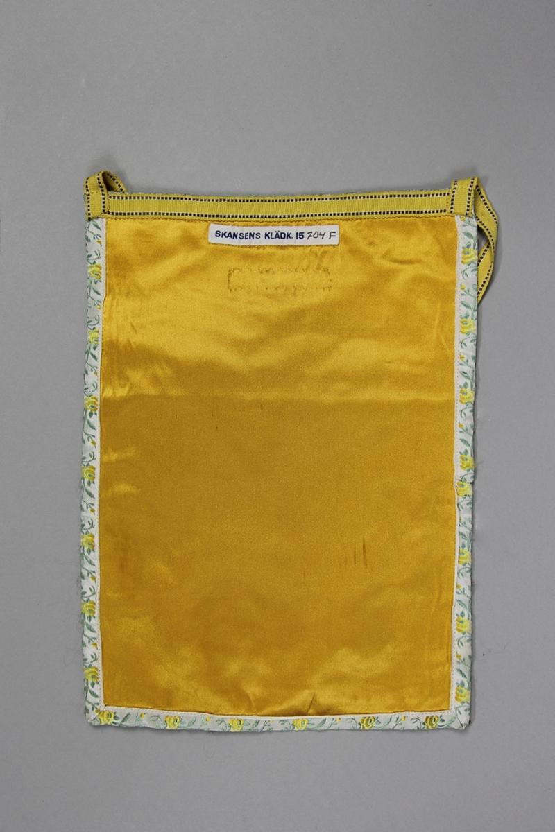 Kjolväska, fyrkantig modell med avskuret framstycke. Tillverkad av gul konstsidensatin med fritt broderi i plattsöm och stjälksöm med konstsilkegarn i många färger. Fickan fodrad med halvlinnetyg, tuskaft. Kantat runtom med jacquardvävt band med blommönster,  i röda och gröna färger på ljus botten. Bakstycket  av samma tyg. Midjeband  av gul bomull med brun kantrand.