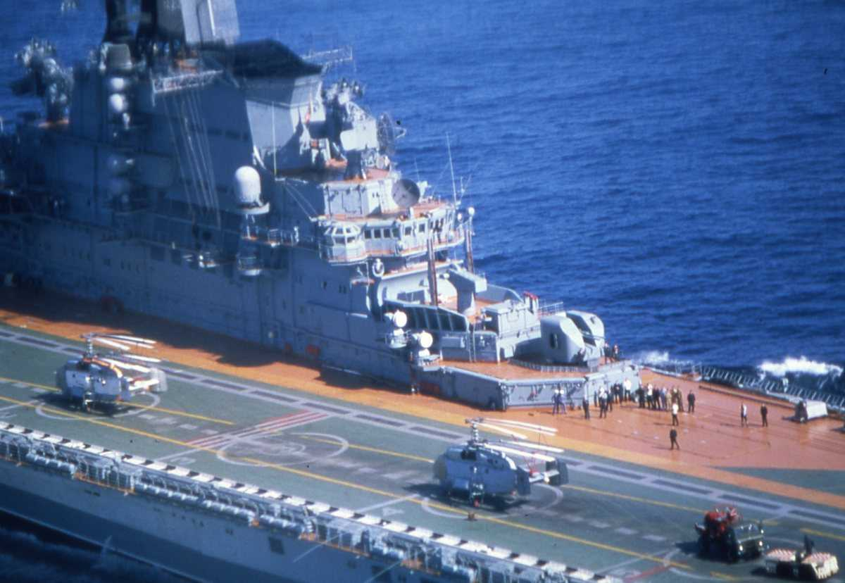 Russisk hangarskip av Kiev - klassen med helikoptere og kjøretøy samt mannskap på flydekket.