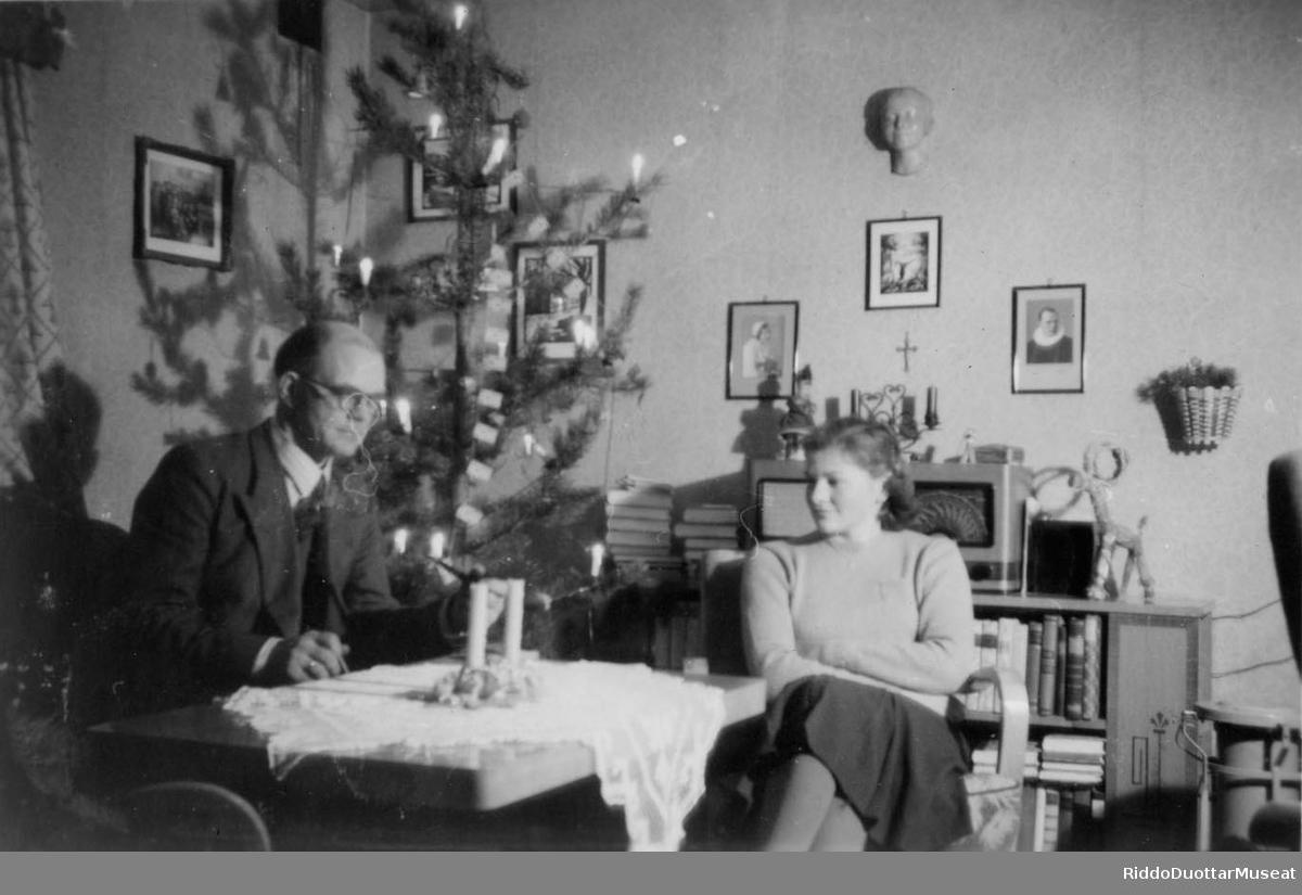Dievdu ja nisu cohkkaba beavdde guoras. Juovlamuorra duogábealde. Mann og en kvinne sitter ved stuebordet. Juletre i bakgrunnen.