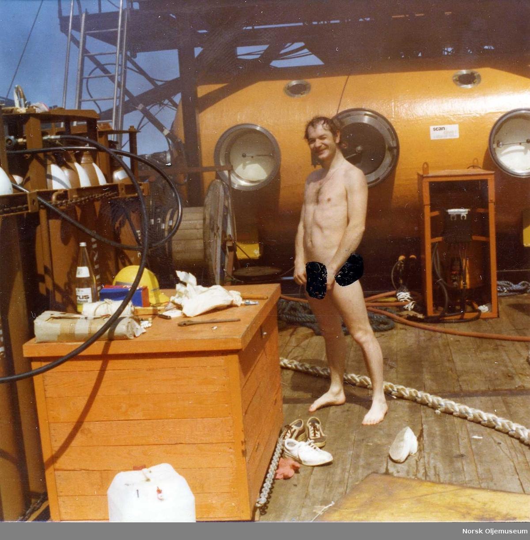 Dykker Geir Ivar Jørgensen på dekk i en litt pinlig positur etter et  dykk.  Arbeidet foregikk ombord på Cod Truck og Scan 600 klokkesystemet kan ses i bakgrunnen. Cut-loose operasjon på Stord for Scan Dive as.