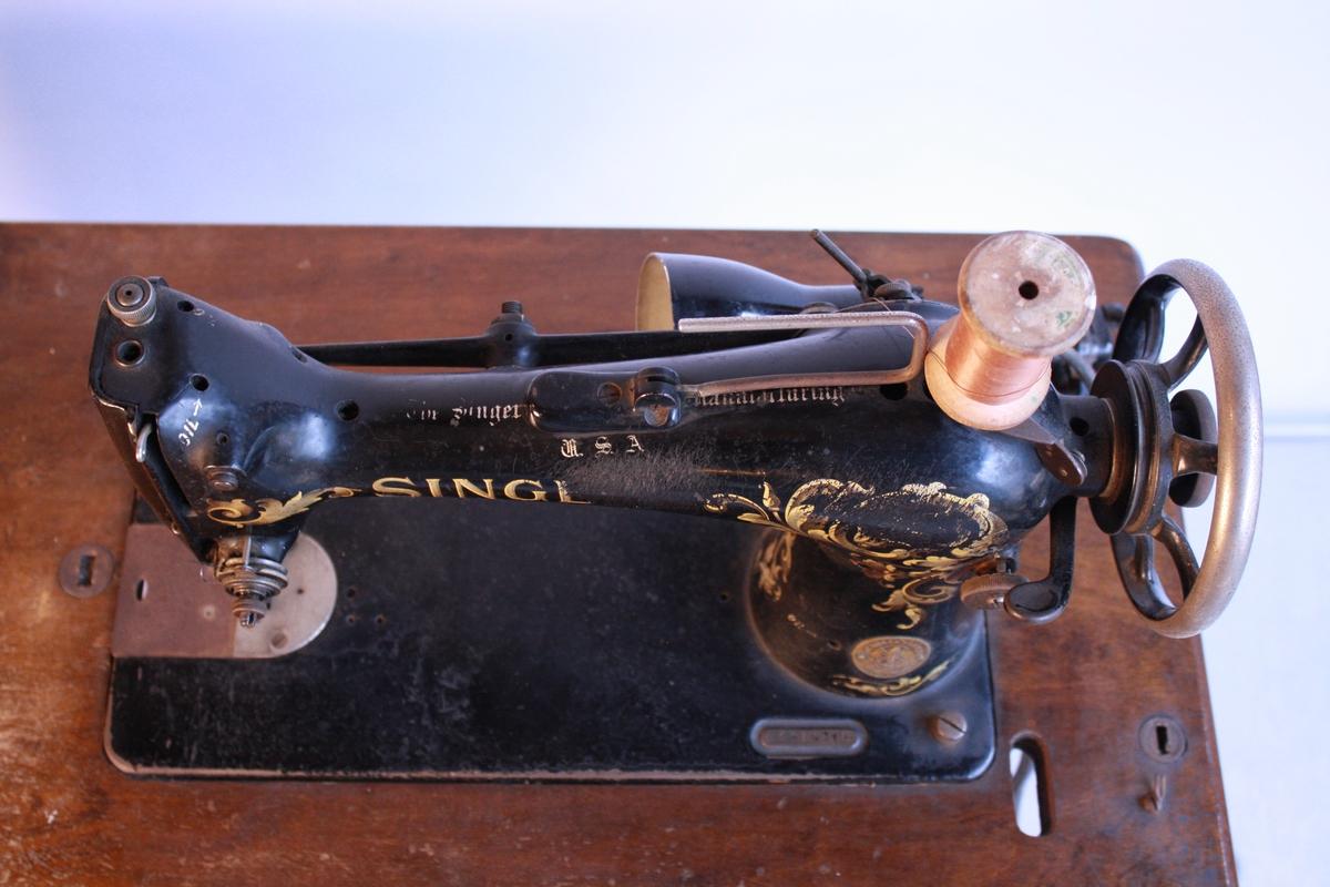 Symaskin fastmontert på bord. Bordet har klaff til å lage større benkplass og ein skuff. Symaskina er modell Singer med dekorasjon i gull, delar av logo og dekorasjon er slitt av. Det er ei lampe på bordet - truleg montert i ettertid. Den er også modernisert med motor som drive drivreima. Drivreima manglar.