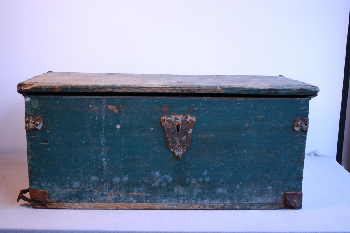 Kiste med flatt lok. Handtak i metall på begge sider. Metallbeslag over lås og hjørner. Metallnagler i lok. Det er skjært inn eit mønster i loket på kista. Den er målt blågrøn. Målinga på loket er slitt. Sett saman med sinking. Blåmålt inni. Har leddik med lok.