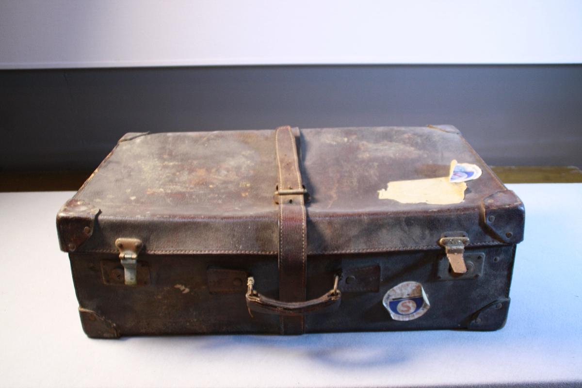 Stor skinnkoffert. Fleire klistermerker og lappar viser at den har vore ute på tur eit par gongar. Den er sett saman med naglar og ekstra forsterka over hjørner. Handtak og to låsar. Ei skinnreim går rundt kofferten til å feste. . Oppbevaringslomme med lok i låk. Det er lagt papir i botn av kofferten.