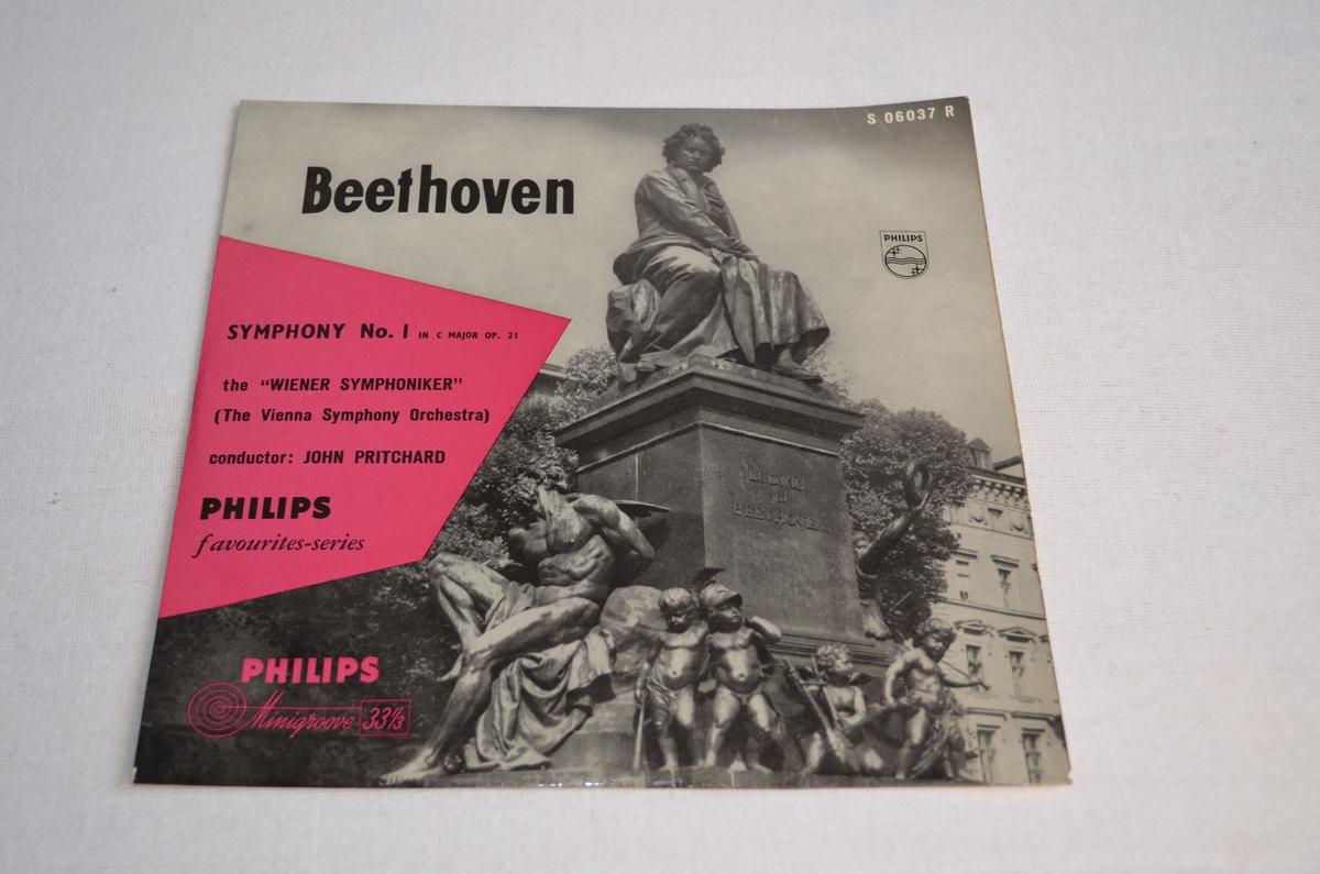 Grammofonplate med etui i papp. På pappetuiet er det bilete av ein statue av Beethoven. Biletet er i svart-kvit medan teksten står i ei rosa rubrikk.
