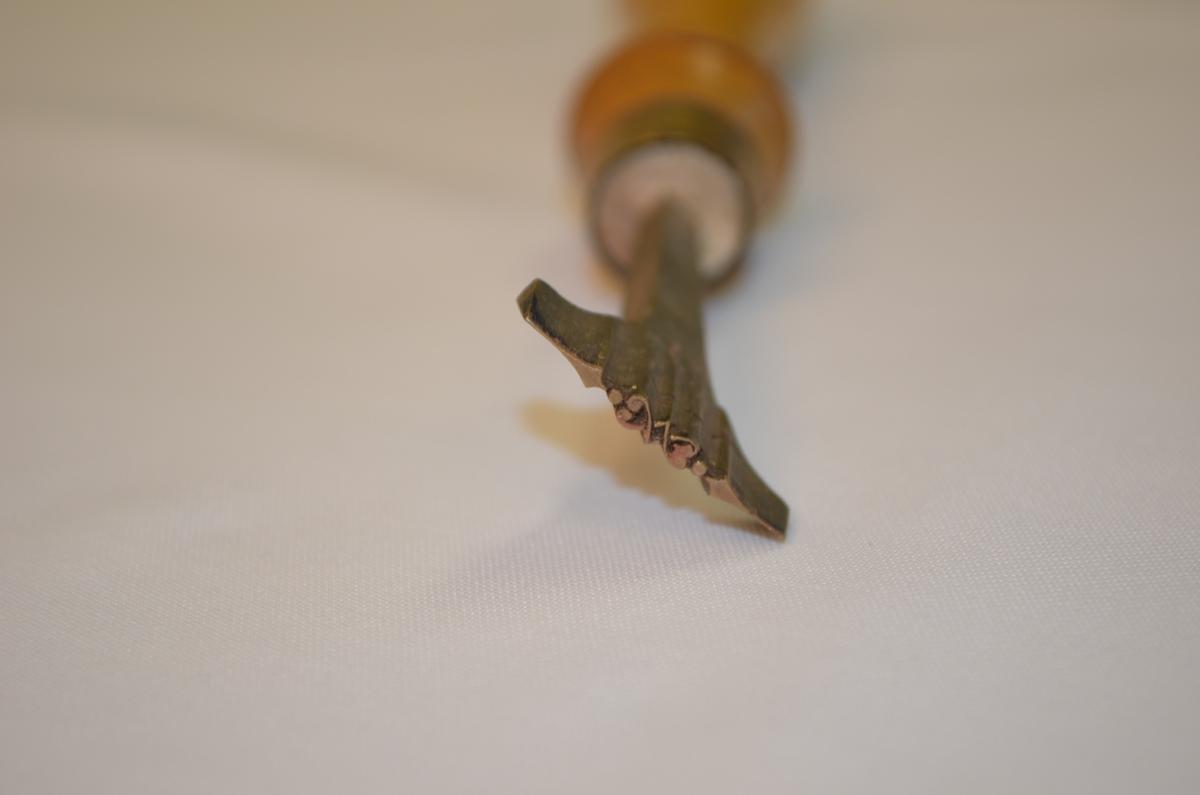 Stempel i jarn med treskaft. Mest truleg nytta til dekorering av skinnpermar til bøker. Denne låg i ei verktøykasse frå ein boktrykkar.